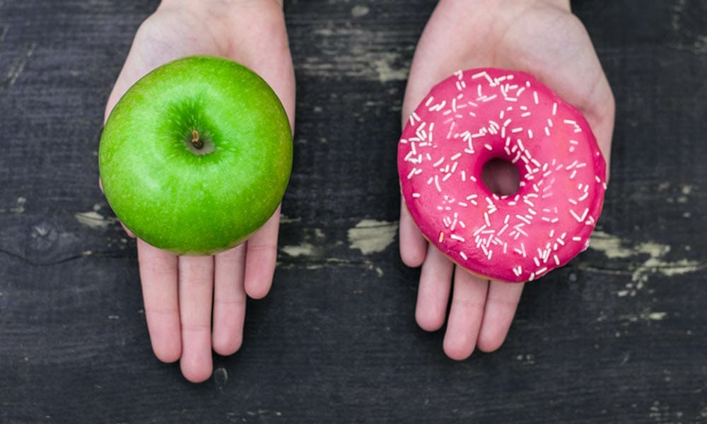 two hands with an apple and a donut
