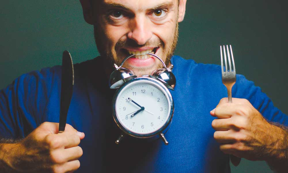 guy holding a clock with his teeth waiting for eating