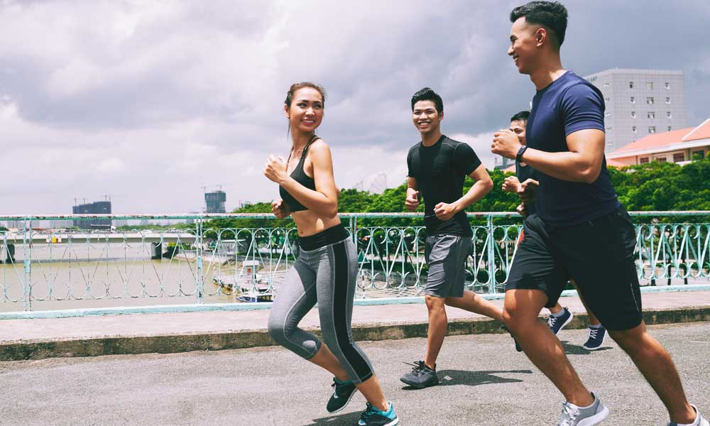 group of asian friends running next to the river